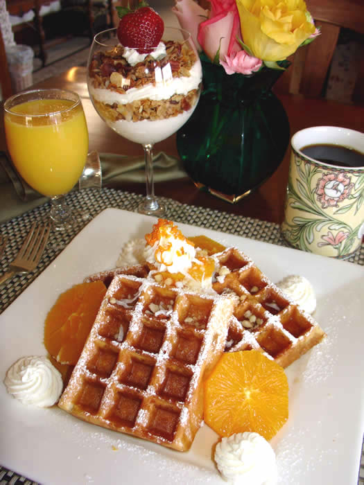Belgian Waffles topped with Toasted  Macadamias, Coconut, Vanilla Bean Whipped Cream  and Grand Marnier Maple Syrup