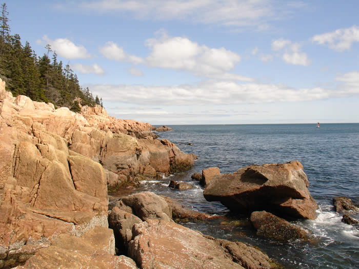 classic coastal Maine with pink granite rock, evergreens and clear blue sky