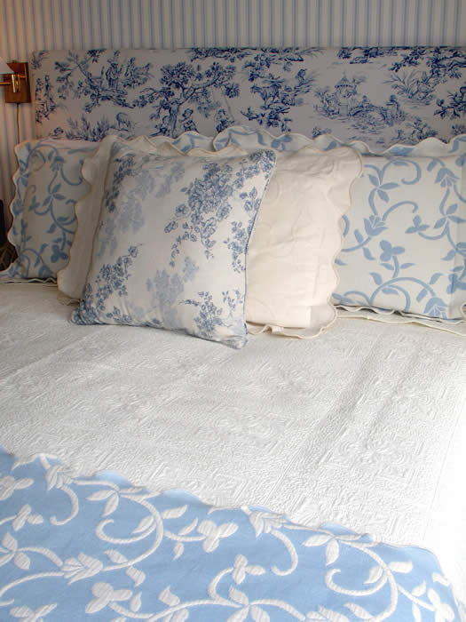 Beautiful layered bedding in 5 various coordinating patterns in shades of blue and white